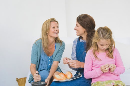 Two women preparing food with a girl at home : Stock Photo