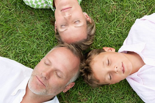 Stock Photo: 1738R-16306 Boy with his parents lying on grass in a park