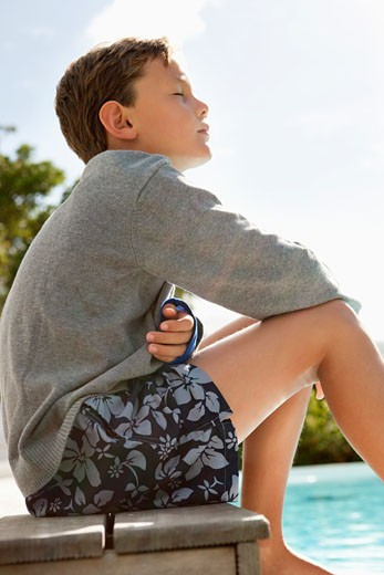 Stock Photo: 1738R-16339 Boy day dreaming near a swimming pool
