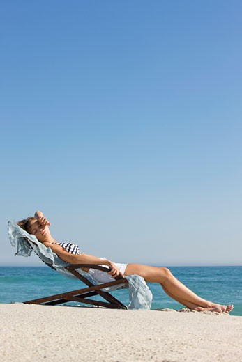 Woman resting in a deck chair : Stock Photo
