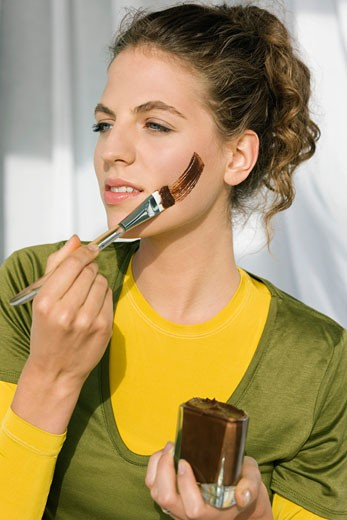Woman applying facial mask with a brush : Stock Photo