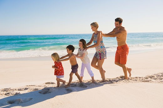 Family walking on the beach in train formation : Stock Photo