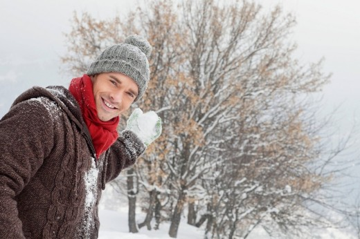 Young man about to throw a snowball : Stock Photo