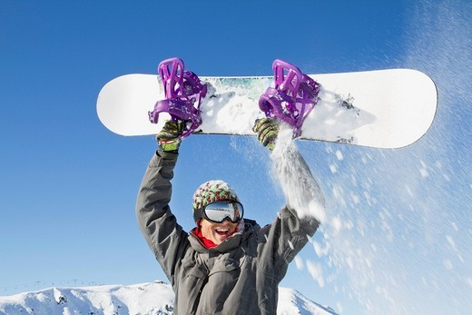 Stock Photo: 1738R-17276 Young man holding his snowboard above his head