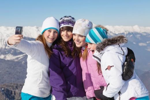 Stock Photo: 1738R-17347 Four teenage girls in ski clothes, taking self portrait