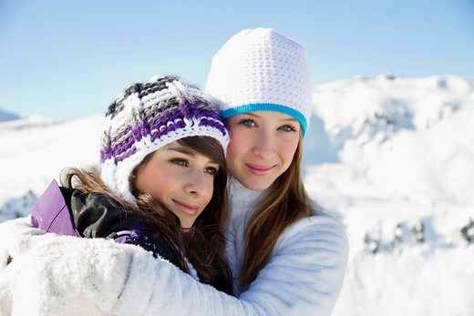 Two teenage girls in winter clothes, embracing : Stock Photo
