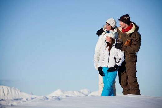 Couple and daughter in ski wear looking away : Stock Photo
