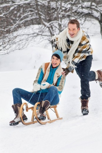 Stock Photo: 1738R-17547 Young man pushing woman on sled
