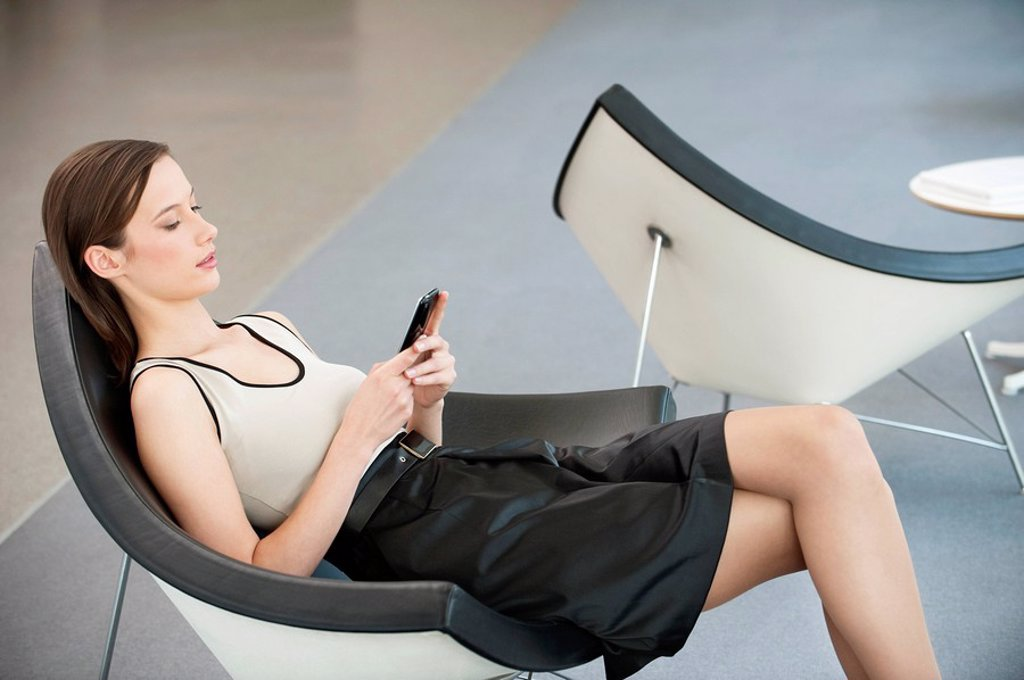 Woman reclining in a chair and text messaging with a mobile phone : Stock Photo