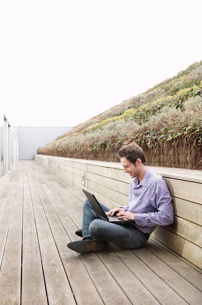 Stock Photo: 1738R-19062 Man using a laptop on a boardwalk