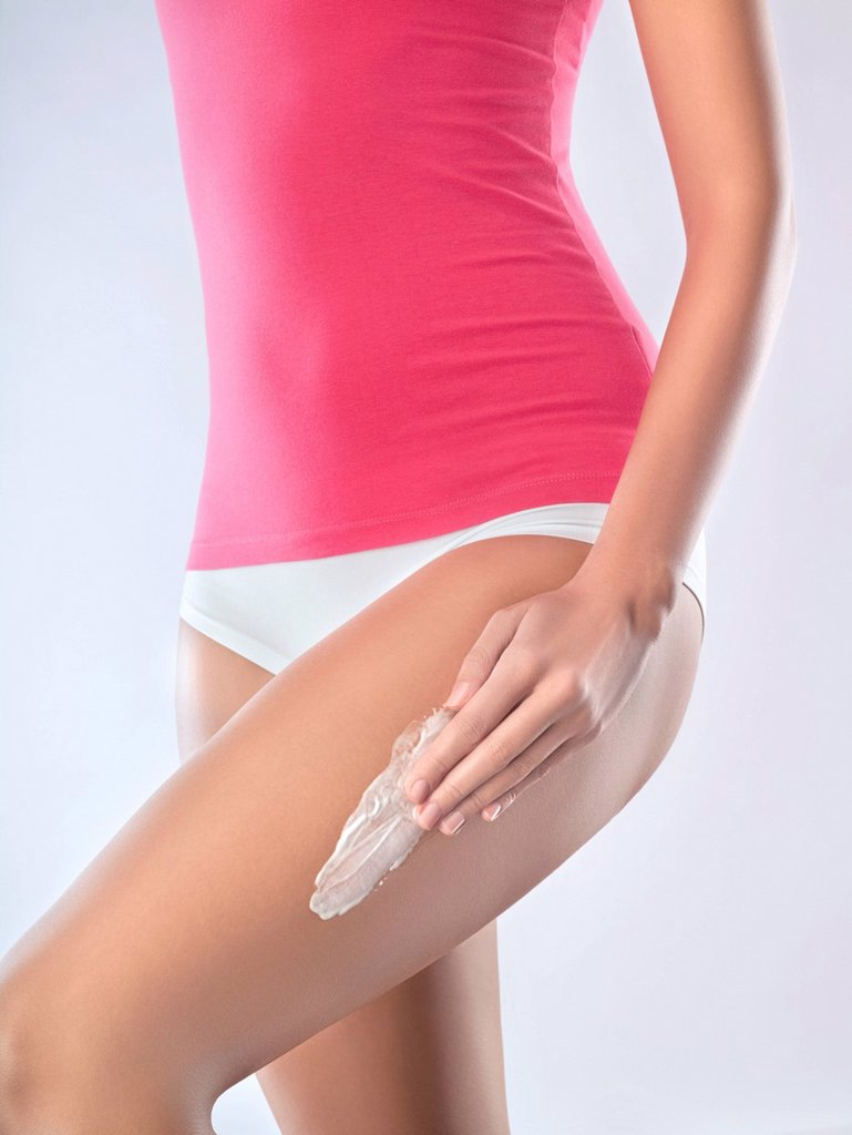 Stock Photo: 1738R-19782 Young woman applying moisturizer to thigh
