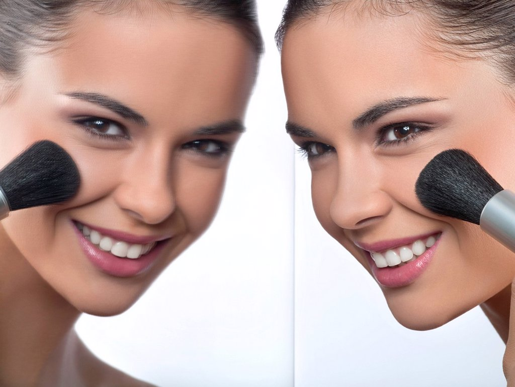 Young woman applying blush and her reflection in mirror : Stock Photo