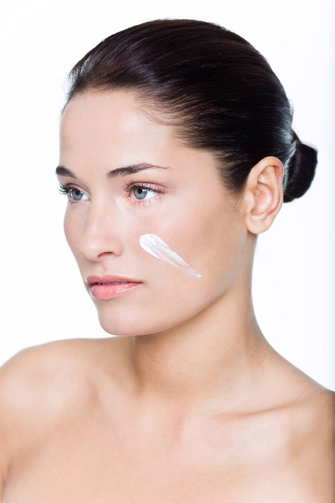 Young woman with moisturizer on her cheek : Stock Photo