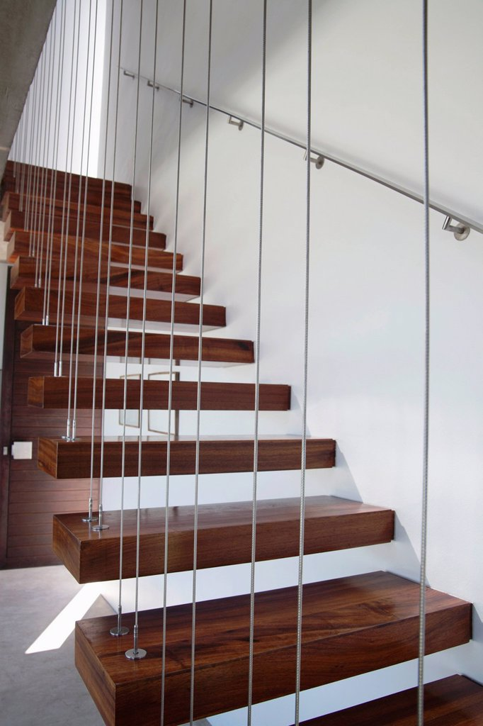 Wooden staircase with white walls and metal railing : Stock Photo