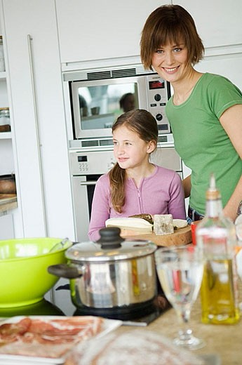 Woman and girl in kitchen : Stock Photo