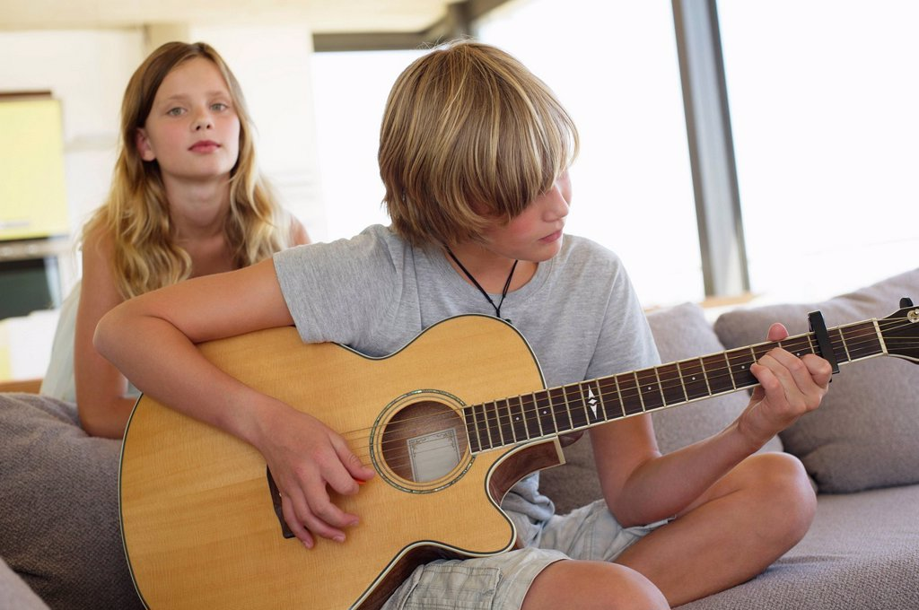 Stock Photo: 1738R-21910 Teenage boy playing a guitar with her sister standing behind him listening