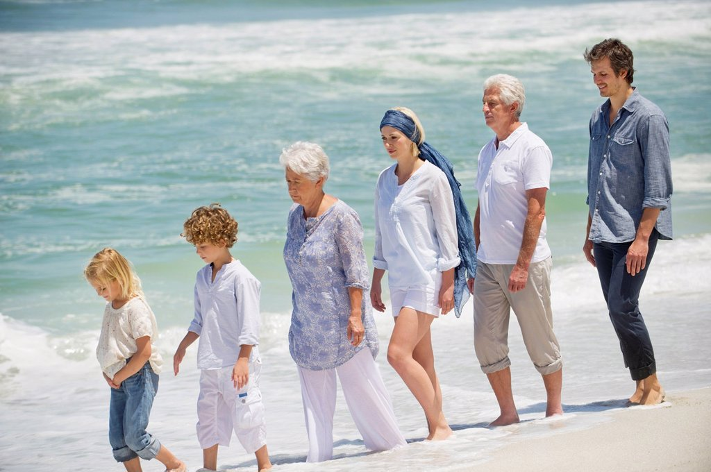 Multi generation family walking in a line on the beach : Stock Photo