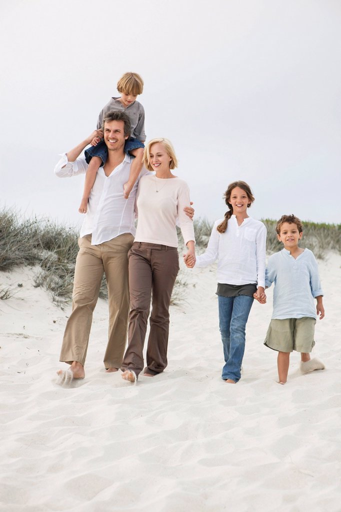 Couple walking on the beach with their children : Stock Photo