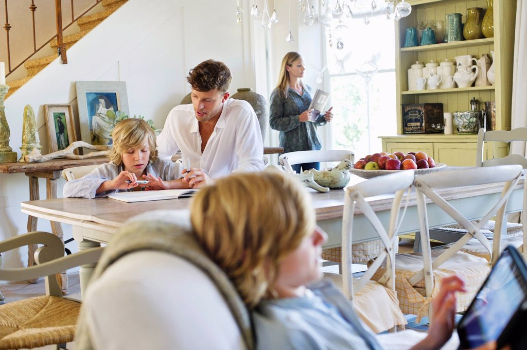 Stock Photo: 1738R-22821 Man teaching little boy while family members busy doing their work at house