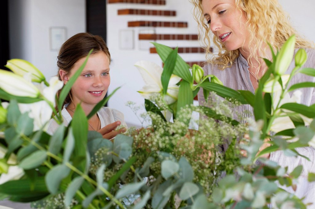 Mid adult woman and her daughter touching leaves : Stock Photo