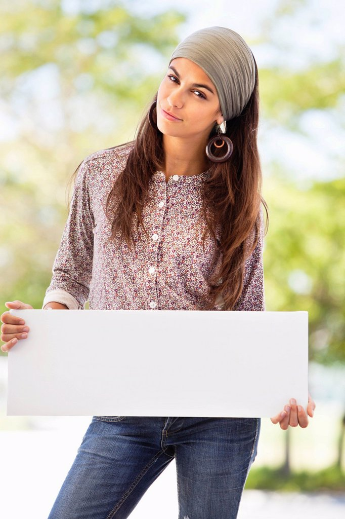 Portrait of a woman holding a blank placard : Stock Photo