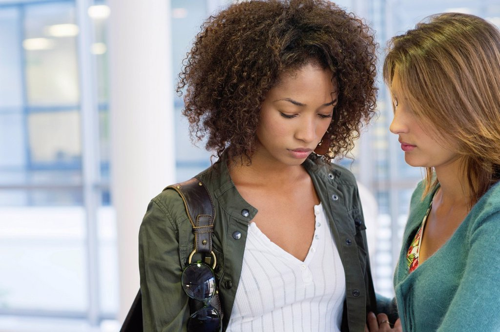 Stock Photo: 1738R-23117 Caucasian woman consoling to an African American woman in university