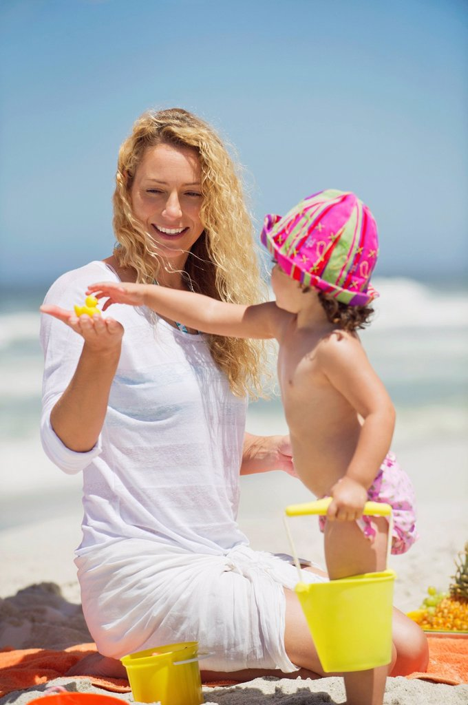 Girl taking toys from her mother hand : Stock Photo