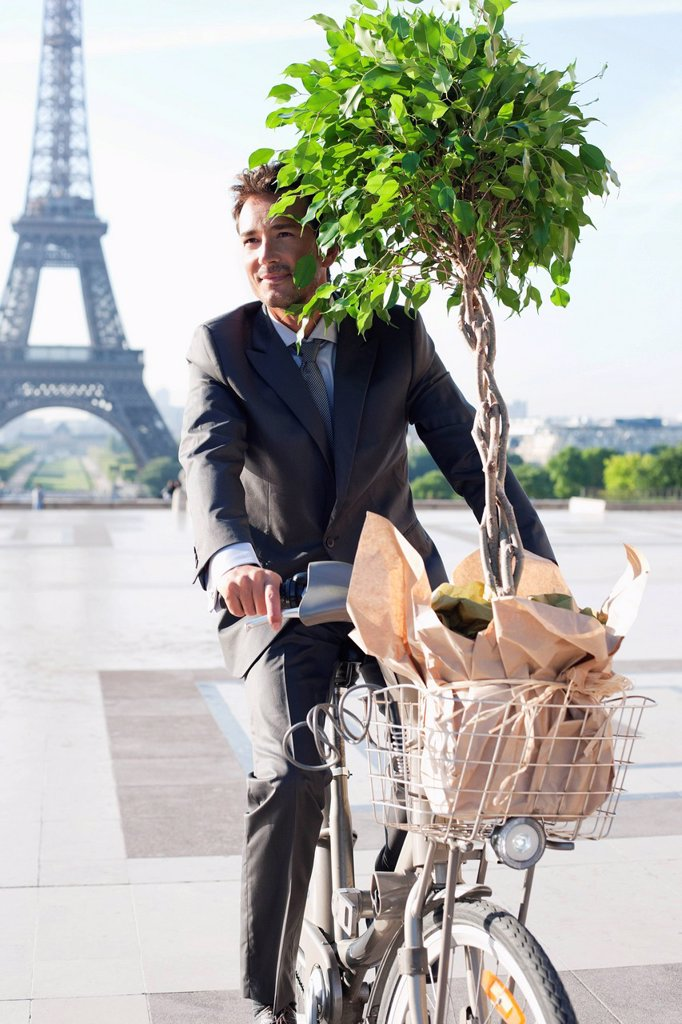 Businessman carrying a plant on a bicycle with the Eiffel Tower in the background, Paris, Ile_de_France, France : Stock Photo