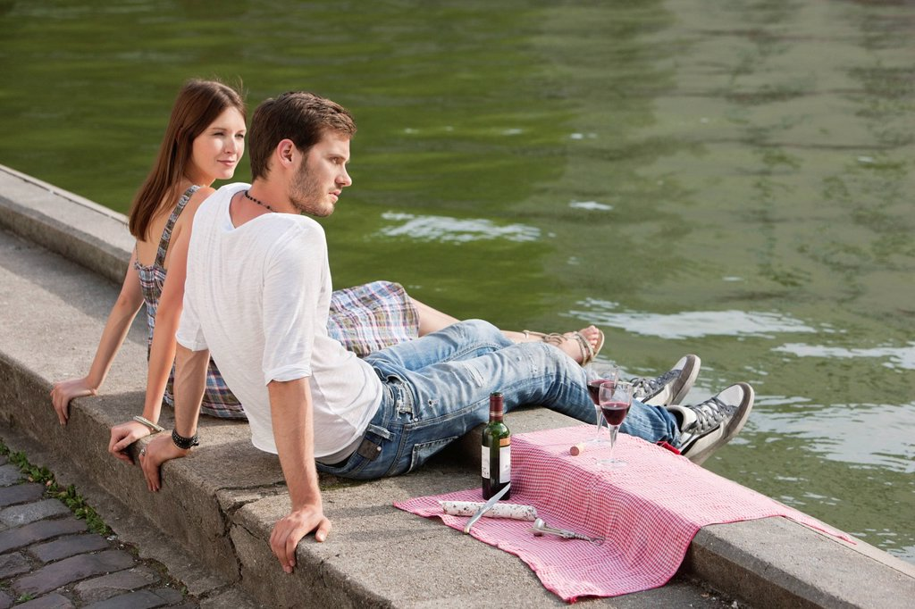Stock Photo: 1738R-24089 Couple sitting at the ledge of a canal, Paris, Ile_de_France, France