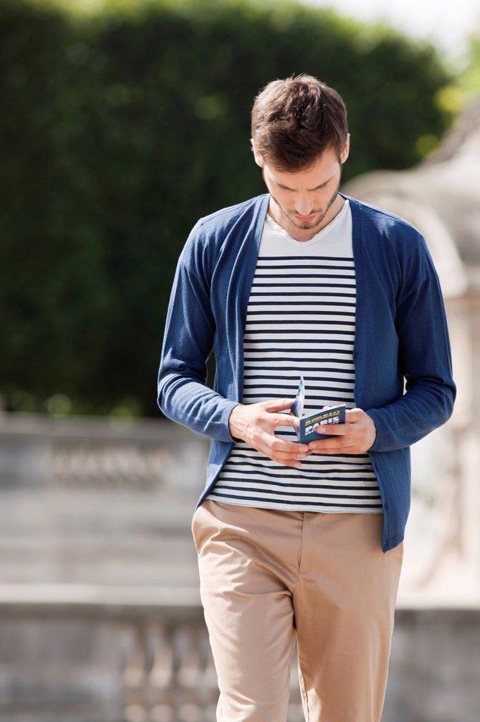 Man reading a travel guidebook, Paris, Ile_de_France, France : Stock Photo