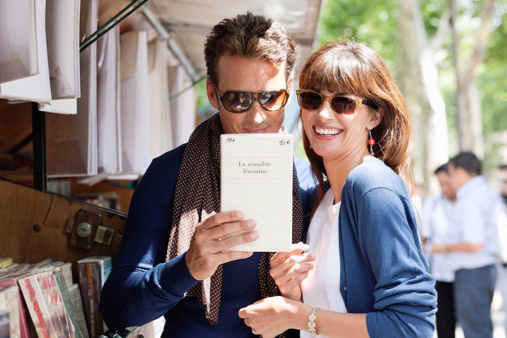 Couple at a book stall, Paris, Ile_de_France, France : Stock Photo