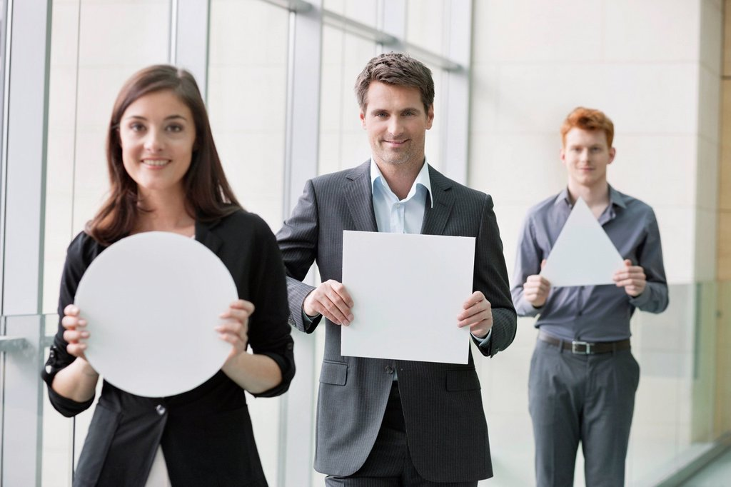 Stock Photo: 1738R-24496 Business executives holding geometrical shaped placards in an office
