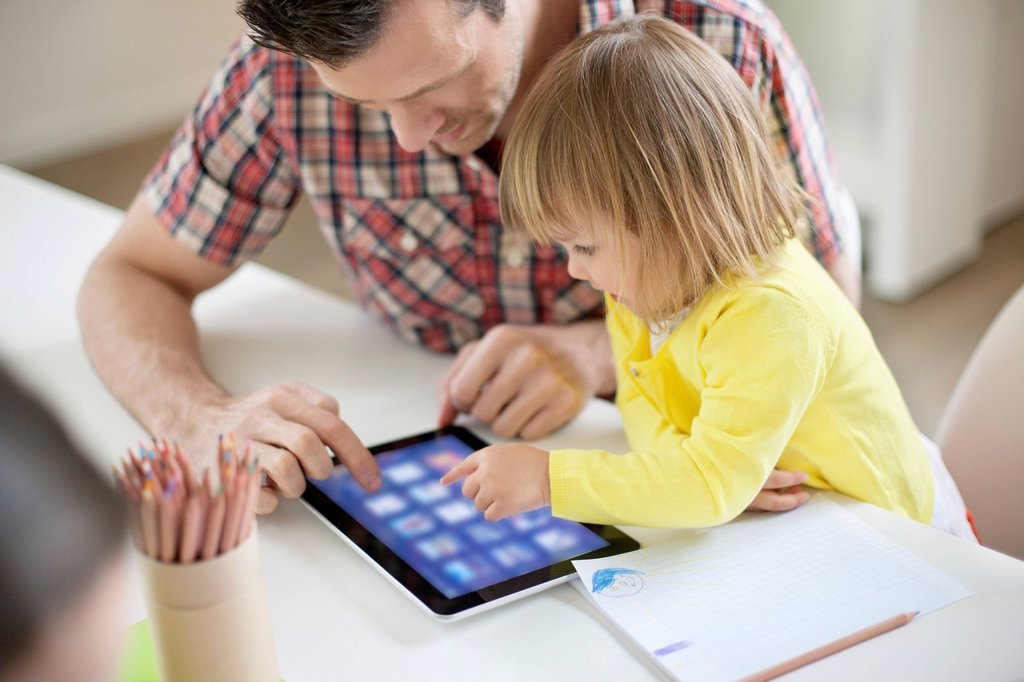 Man teaching digital tablet to his daughter : Stock Photo