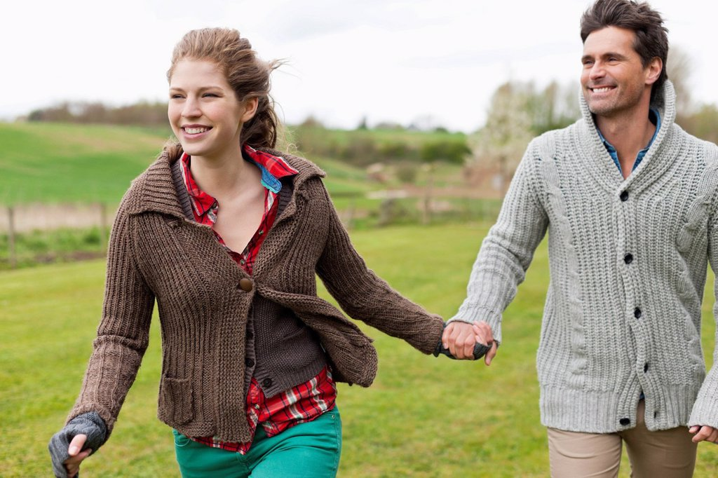 Couple holding hands in a field : Stock Photo