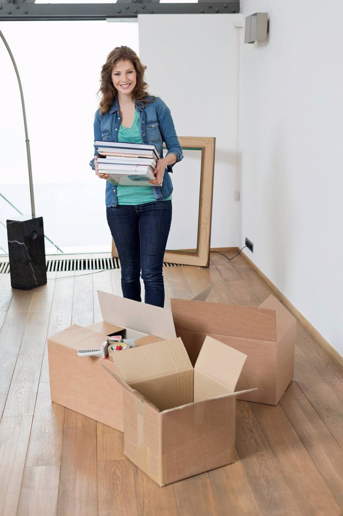 Stock Photo: 1738R-24578 Woman carrying stack of magazines