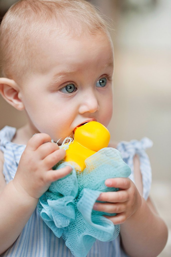Close_up of a baby girl playing with a toy : Stock Photo