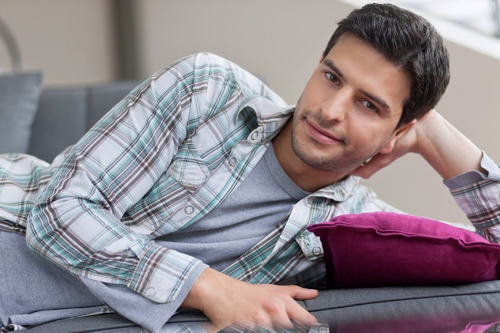 Portrait of a man lying on a couch : Stock Photo