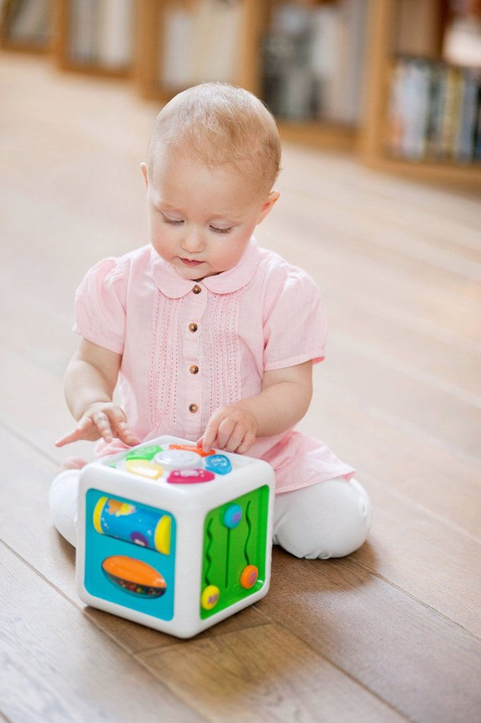 Baby girl playing with a musical block toy : Stock Photo