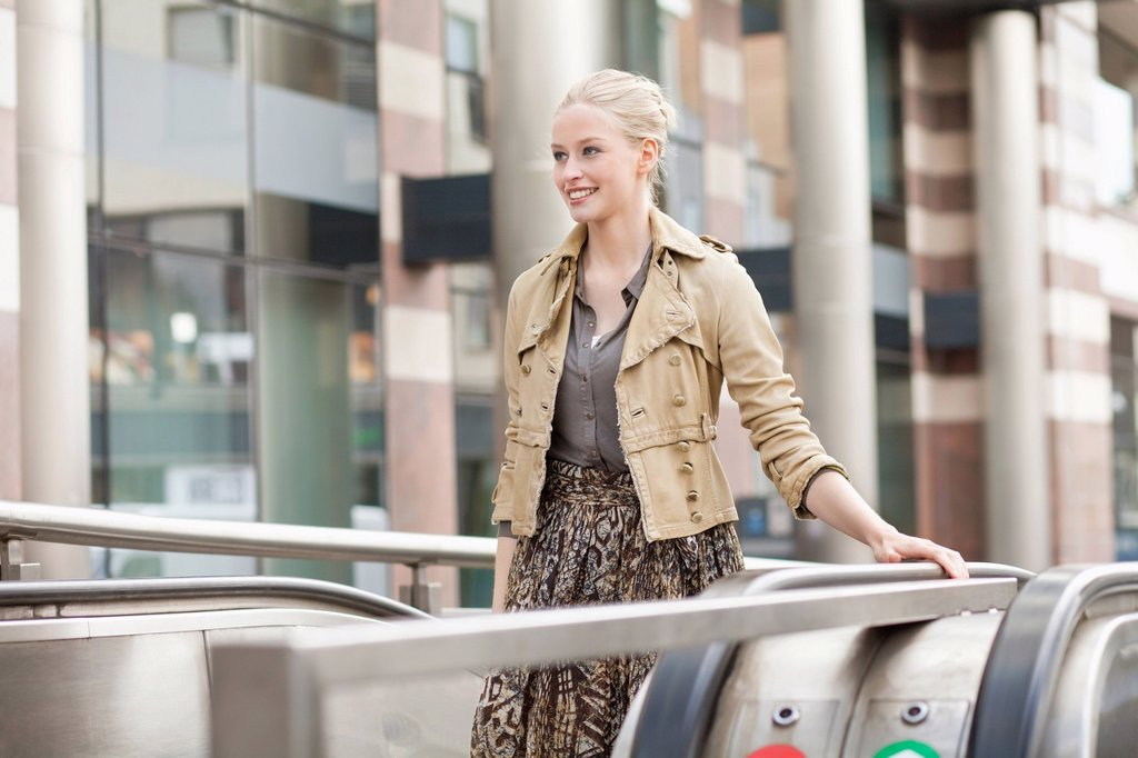 Stock Photo: 1738R-24691 Businesswoman standing on escalator