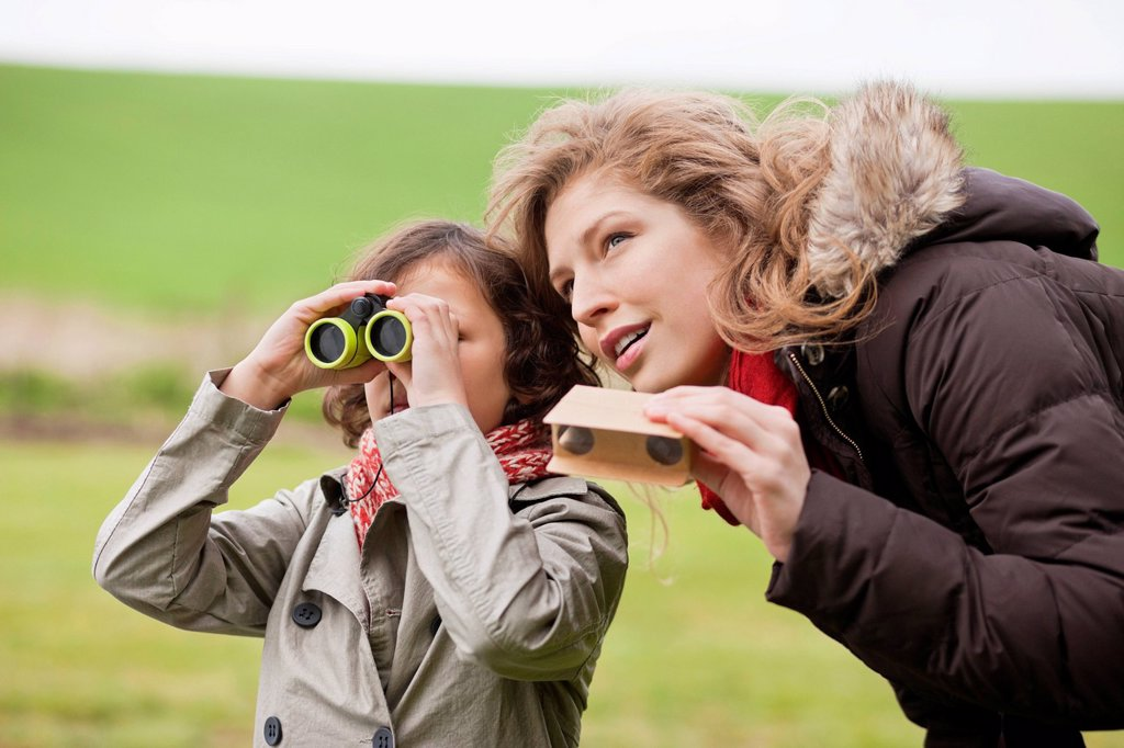 Stock Photo: 1738R-24932 Boy looking through binoculars standing with his mother