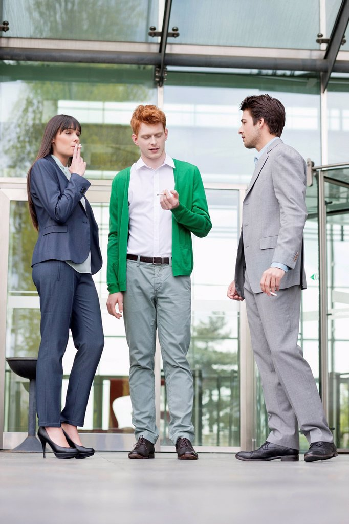 Business executives smoking in front of an office building : Stock Photo
