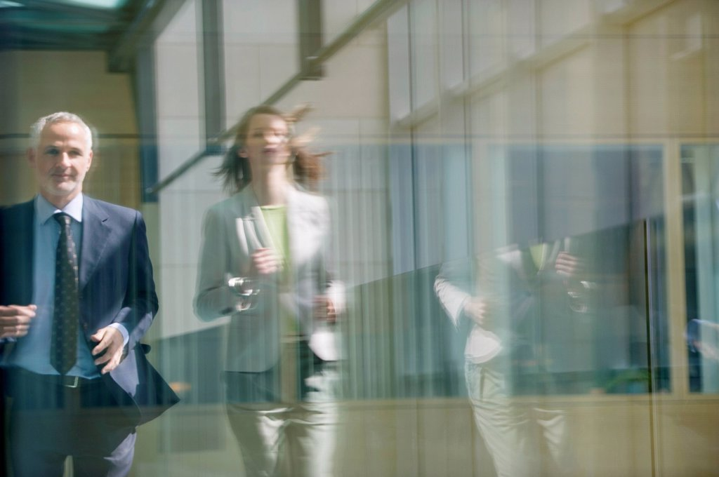 Stock Photo: 1738R-25088 Two business executives running in the corridor