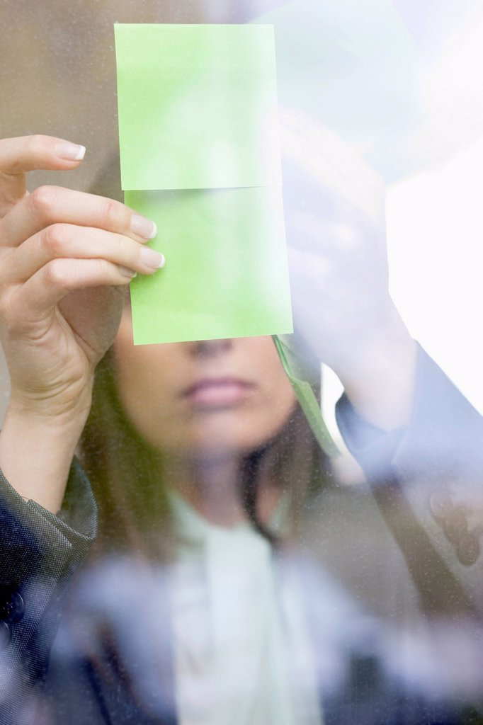Businesswoman sticking memo notes on glass in an office : Stock Photo