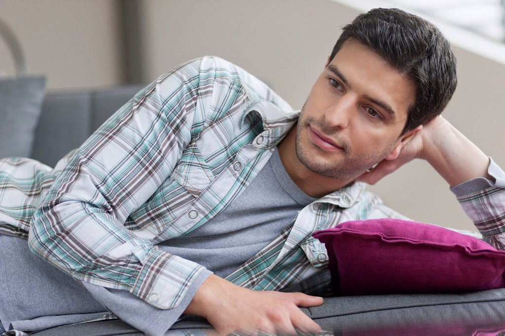 Stock Photo: 1738R-25246 Man lying on a couch and thinking