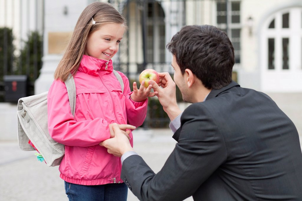 Stock Photo: 1738R-25335 Man giving an apple to his daughter