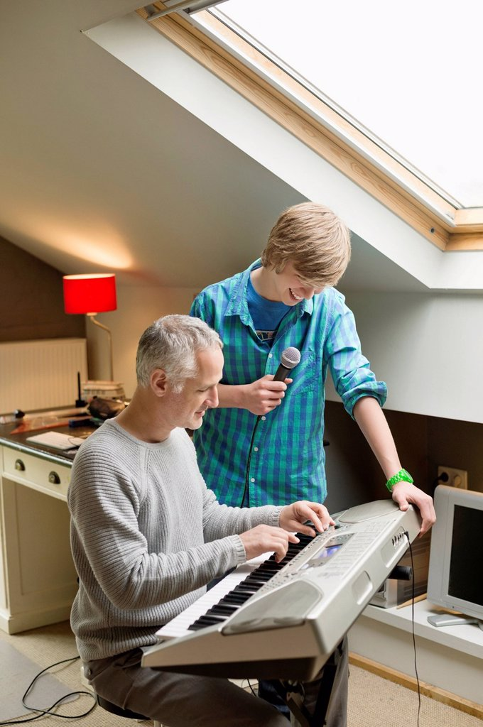 Stock Photo: 1738R-25687 Man playing an electric piano with his son at home