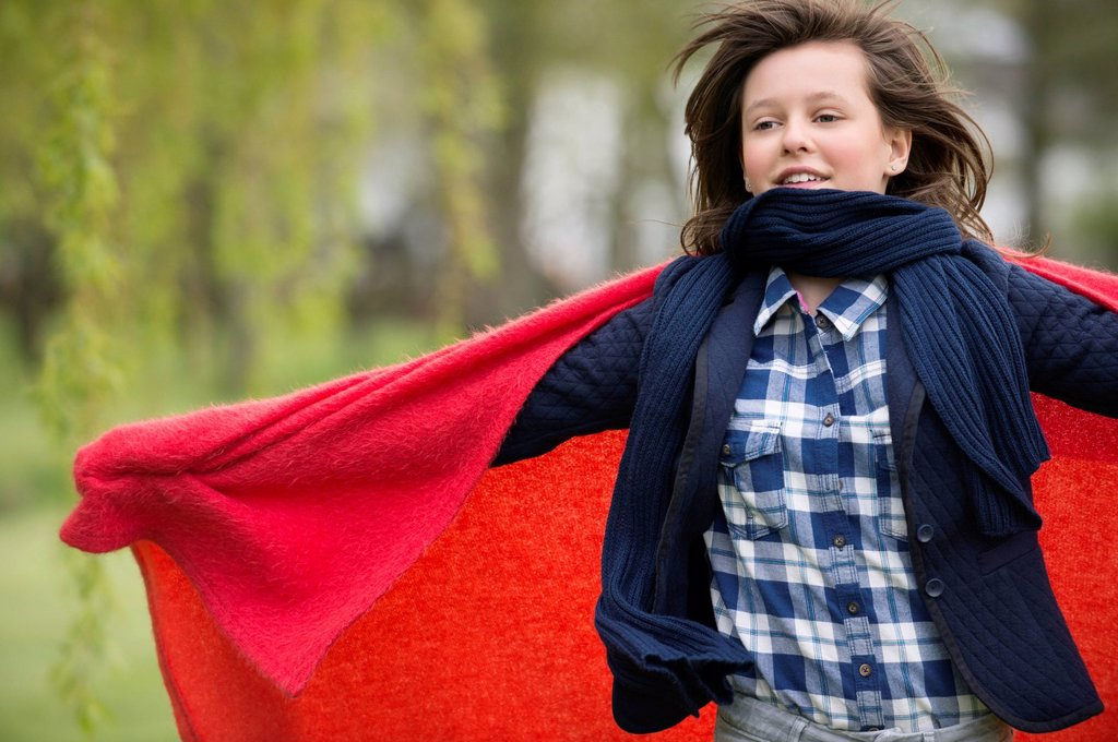 Girl holding a blanket with her arm outstretched : Stock Photo