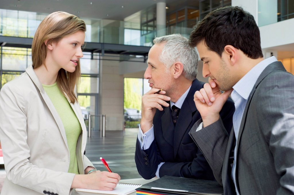 Business executives discussing in an office : Stock Photo