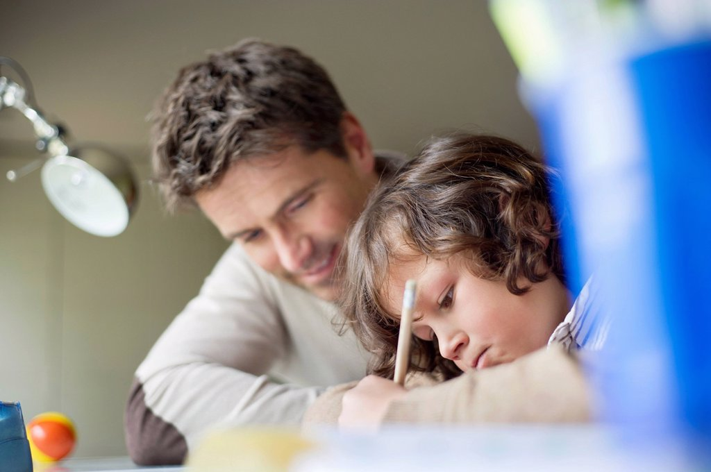 Stock Photo: 1738R-26060 Boy studying with his father at home