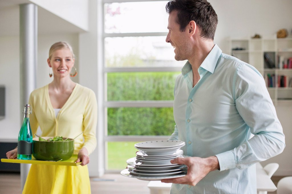 Stock Photo: 1738R-26141 Couple carrying food and plates for serving